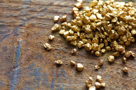 foto of primite  - a mound of gold on a old wooden work table - JPG