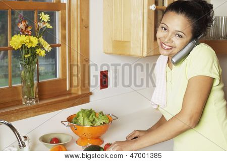 Young woman chopping vegetables and talking on the phone