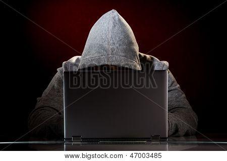 Hacker em um óculos de sol com o laptop.
