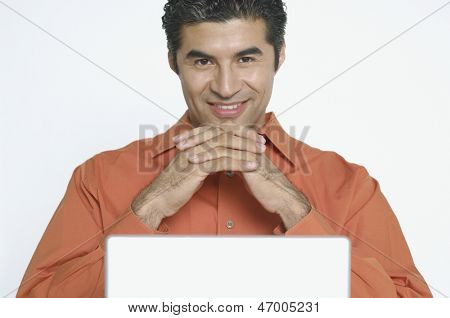 Young man smiling for the camera while using a laptop
