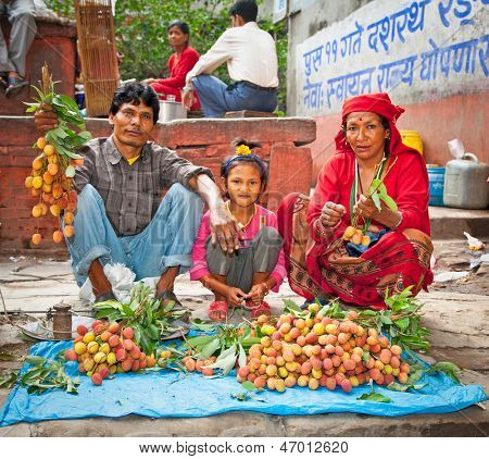 KATHMANDU, NEPAL - MAY 19: Family sell lychee fruits on a street market in Kathmandu on May 19, 2013. On United Nations list Nepal as one of the Least developed country in the world.