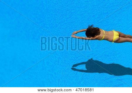 Top view of a girl diving in the swimming pool