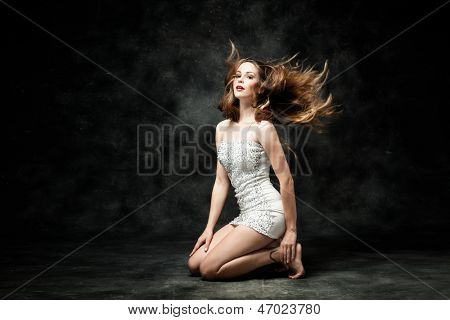 beautiful young woman in white dress and fluttering hair studio dark background