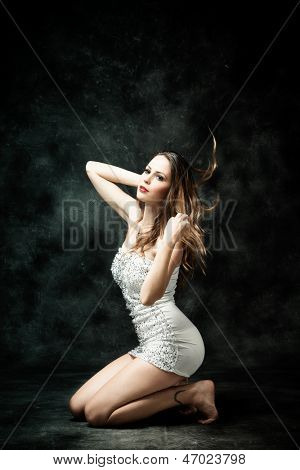 beautiful young woman in short white dress studio dark background
