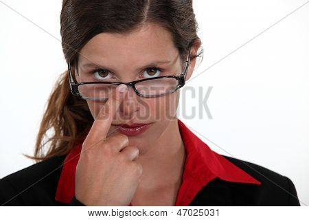 A businesswoman repositioning her glasses.