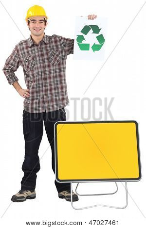 Manual worker stood with recycle poster