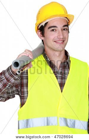 Construction worker carrying tubes