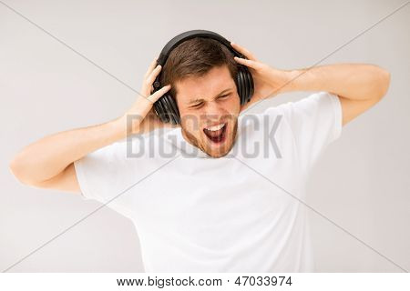 young man with headphones listening loud music
