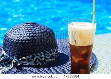 Ice coffee Freddo against blue clear water of the swimming pool with straw hat
