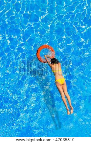 Young woman jumping in the buoy at the swimming pool
