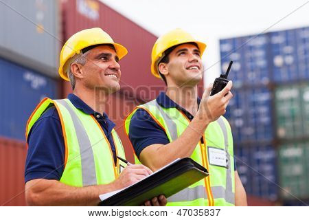 two harbor workers monitoring containers loading