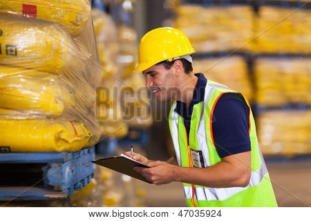 smiling young worker recording rice stock before delivery