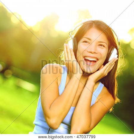 Woman listening to music in headphones in park in beautiful sunlight on sunny day. Happy joyful asian woman singing outside.