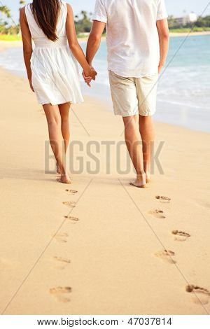 Couple holding hands walking romantic on beach on vacation travel holidays leaving footprints in the sand. Closeup of feet and golden sand for copy space. Young couple wearing white shorts.