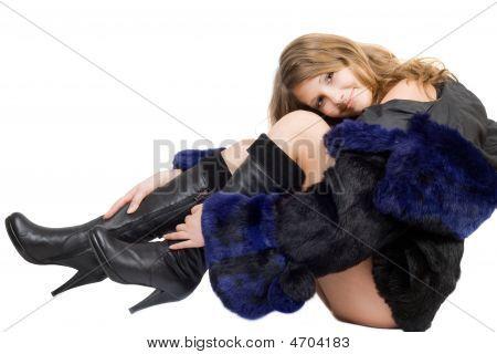 schönes lächelnd mädchen in einem Pelzmantel und Stiefel