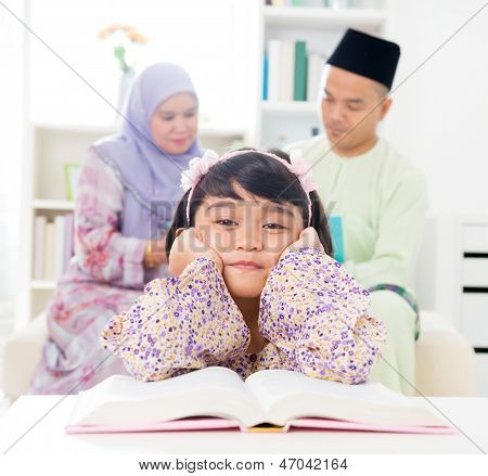 Malay girl reading book. Southeast Asian family at home. Muslim parents and child living lifestyle.