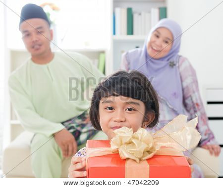 Southeast Asian girl with gift box. Muslim family living lifestyle. Happy smiling Malay parents and child.