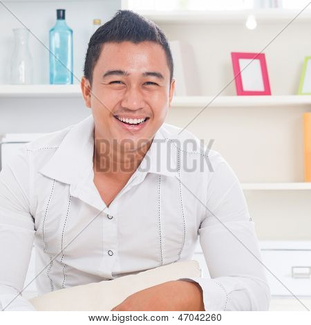 Good looking young Asian man smiling happy. Lifestyle Southeast Asian man at home. Handsome Asian male model.