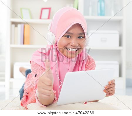 Asian teen listening to music with headphone and thumb up. Southeast Asian teenager at home. Muslim teenage girl living lifestyle.