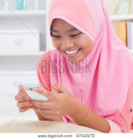 Asian teen texting on the phone. Southeast Asian teenager at home. Muslim teenage girl living lifestyle.