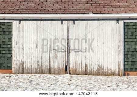 Old weathered barn doors on a rustic barn in winter.