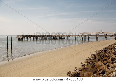 Pier And Empty Beach Beyond Seawall