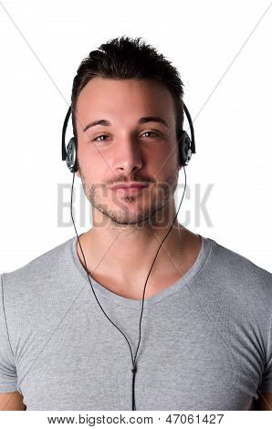 Attractive Smiling Young Man Listening To Music With Headphones