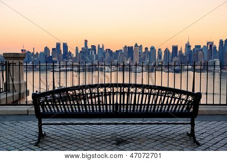 Banco no parque e New York City midtown Manhattan ao pôr do sol com horizonte panorama vista sobre Hudson R