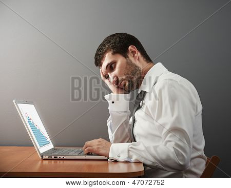sorrowful businessman looking at his laptop