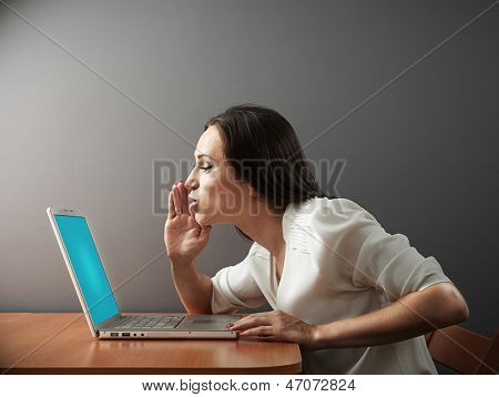 young woman whispering secrets to her laptop
