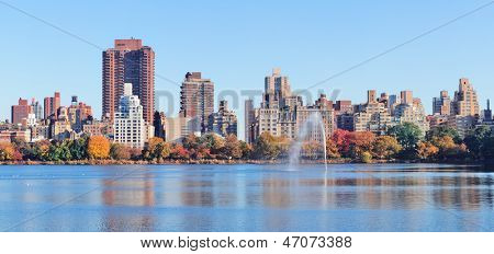 New York City Manhattan Central Park midtown skyline panorama over lake with fountain and blue clear sky in Autumn.