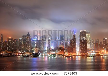 New York City Manhattan midtown Times Square skyline at night with skyscrapers over Hudson River viewed from New Jersey.