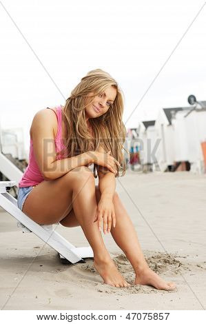 Young Woman Sitting On Steps At The Beach With Barefeet In Sand