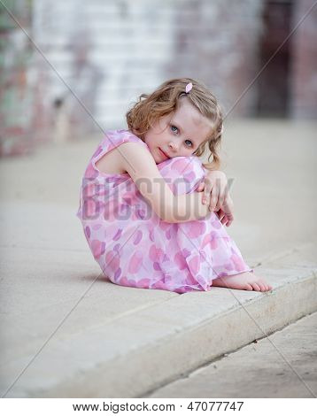 Little Girl on Curb Hugging Knees