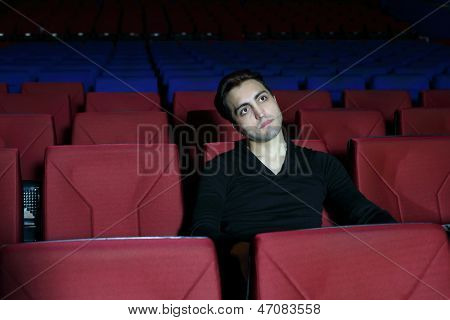 Young serious man in black watches movie in big cinema theater.