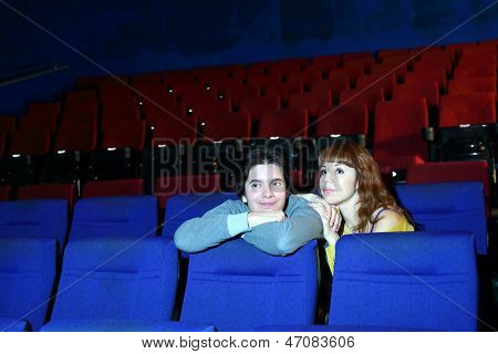 Smiling young man and focused woman watch movie in cinema theater.