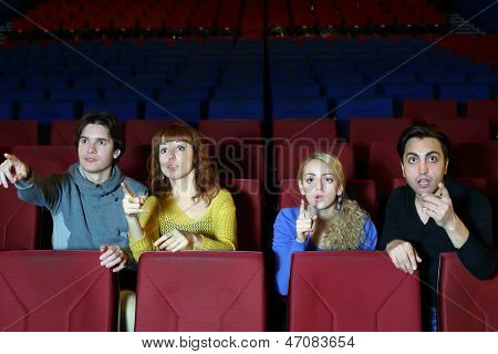 Four young friends amaze and point finger at screen in cinema theater.