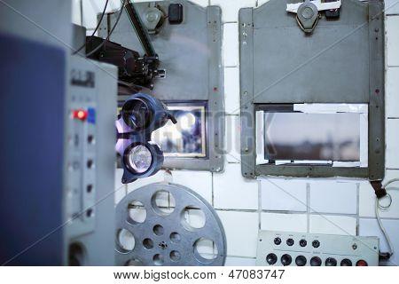 Proyector y carretes de cinta en la pequeña sala de cine antiguo.