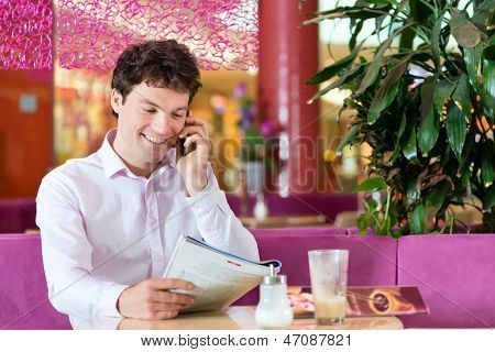 Young man in a cafe or ice cream parlor reading a magazine and using his phone, maybe he is single or waiting for someone
