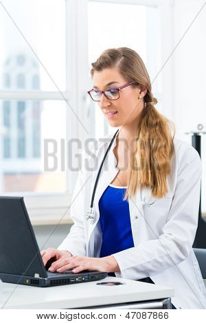 Young female doctor sitting at a desk in front of window in clinic writing or reading on a Computer or laptop