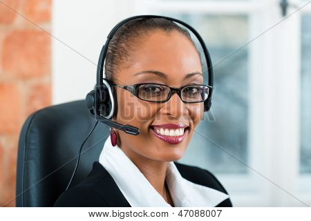 Young businesswoman or secretary working in her Office with a headset, she has a customer pitch