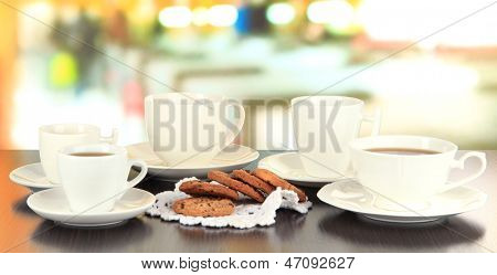 Cups of coffee and cookies on napkin on dark table on room  background