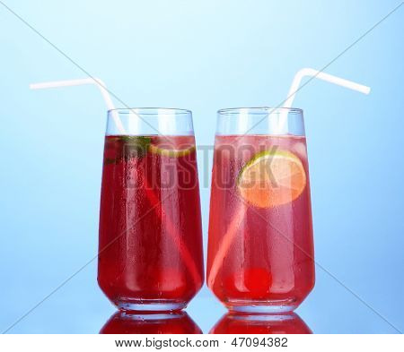 Two cherry cocktails with ice on dark blue background