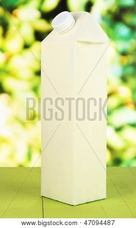 Milk pack on table on bright background