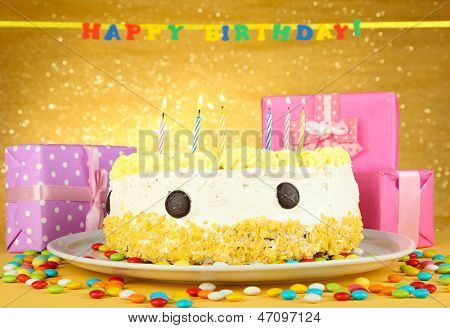 Happy birthday cake and gifts, on yellow background