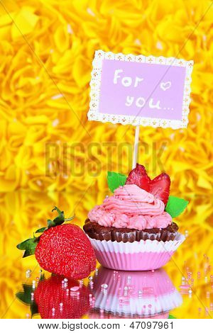 Beautiful strawberry cupcake with postcard on decorative yellow background