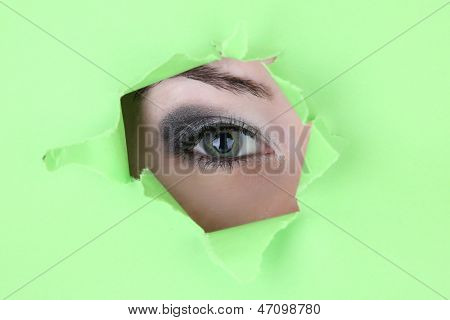 Female eye looking through hole in sheet of paper