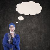 stock photo of muslimah  - Thoughtful female muslim thinking and blank cloud on chalkboard background - JPG