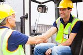 stock photo of forklift driver  - two warehouse forklift drivers handshaking when shift change over - JPG
