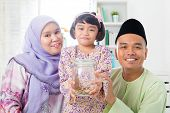 image of malay  - Southeast Asian Malay family saving money at home - JPG